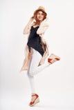一个帽子的年轻美丽的妇女在白色背景,全长,跃迁,时尚 免版税库存图片