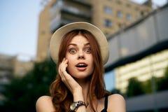 一个帽子的年轻美丽的妇女在街道上在城市,画象 库存图片