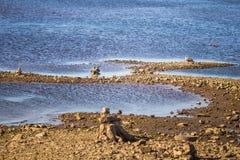 一个干河床和岩石的晴朗的河沿风景 在河附近的石平衡的建筑 免版税图库摄影
