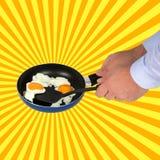 一个平底锅 拿着一个长柄浅锅用煎蛋的手 免版税库存图片
