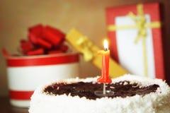 一个年生日 与灼烧的蜡烛和礼物的蛋糕 库存照片
