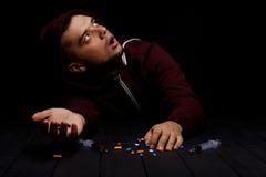 一个年轻上瘾者男性是沮丧和惊吓在黑背景 有很多麻醉药品的一个人在桌上 库存照片