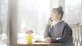 一个年轻严肃的逗人喜爱的深色的女孩有一个电话在咖啡馆 免版税库存图片