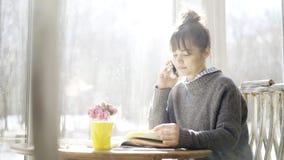 一个年轻严肃的逗人喜爱的深色的女孩有一个电话在咖啡馆 库存照片