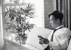 一个年轻亚洲商人等待咖啡馆的一个伙伴 Bu 库存图片