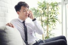 一个年轻亚洲商人等待咖啡馆的一个伙伴 Bu 免版税库存图片