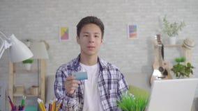 一个年轻亚裔人工作在膝上型计算机并且举行一万一银行卡在房子的客厅和神色在照相机 股票录像