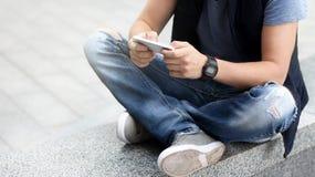 一个年轻人使用他的智能手机,当坐沥青时 免版税库存照片