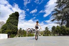 一个年轻人做在他的BMX自行车的把戏 免版税库存照片