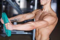 一个年轻人做着一锻炼用从一个酒吧特写镜头的一个薄煎饼在健身房的被弄脏的背景 图库摄影