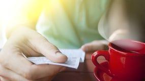 一个年轻人在一个晴朗的夏天早晨审查在一个咖啡馆的票据 库存照片