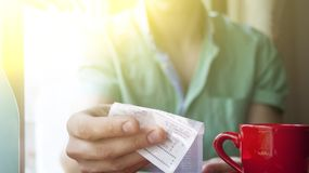一个年轻人在一个晴朗的夏天早晨审查在一个咖啡馆的票据 库存图片