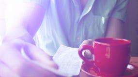 一个年轻人在一个晴朗的夏天早晨审查在一个咖啡馆的票据 免版税库存照片