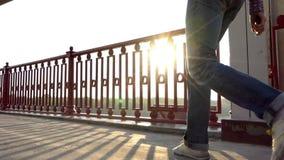 一个年轻人在一座桥梁努力去做以跳舞方式在慢动作的日落 股票录像
