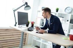 一个年轻人在一张桌附近在他的手上站立在办公室,拿着一支铅笔并且与文件和计算机一起使用 库存照片