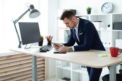 一个年轻人在一张桌附近在他的手上站立在办公室,拿着一支铅笔并且与文件和计算机一起使用 免版税库存照片