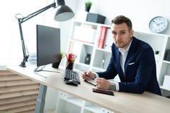 一个年轻人在一张桌附近在他的手上站立在办公室,拿着一支铅笔并且与文件和计算机一起使用 库存图片