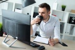 一个年轻人在一张桌附近在他的手上站立在办公室,拿着一支铅笔并且喝咖啡 一个年轻人工作与 免版税库存图片