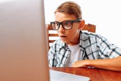 一个年轻人在与膝上型计算机的一张桌上,被冲击由什么他看见了,青少年的惊奇的神色在膝上型计算机,坐白色背景在 免版税库存图片
