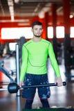 一个年轻人在与锤子的健身房训练 免版税库存照片