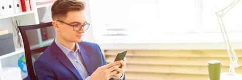 一个年轻人在他的手上坐与一个电话在一张桌上在办公室 免版税库存照片