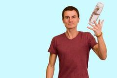 一个年轻人在他的手上拿着一个瓶水 库存图片