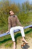 一个年轻人在公园坐 库存图片
