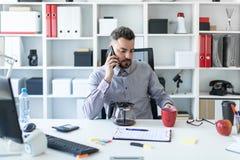 一个年轻人在办公室在他的手上在桌上,谈话坐电话和拿着一个红色杯子 免版税库存照片