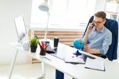一个年轻人在办公室在计算机书桌,谈话坐电话和看地球 库存照片
