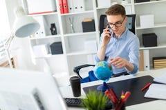一个年轻人在办公室在计算机书桌,谈话坐电话和看地球 免版税库存照片