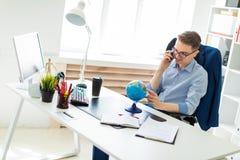 一个年轻人在办公室在计算机书桌,谈话坐电话和看地球 免版税图库摄影