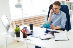 一个年轻人在办公室在计算机书桌,谈话坐电话和看地球 图库摄影