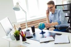 一个年轻人在办公室在计算机书桌,谈话坐电话和看地球 库存图片