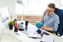 一个年轻人在办公室在计算机书桌,谈话坐电话和看地球 免版税库存图片