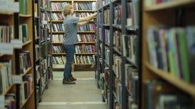 一个年轻人在图书馆里选择一本书 许多书,他是在书系列之间的走廊 股票录像