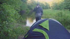 一个年轻人在帐篷和森林河附近喝从热水瓶杯子的茶 股票视频