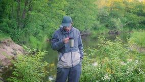 一个年轻人在森林河附近喝从热水瓶杯子的茶 影视素材