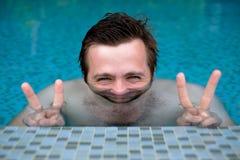 一个年轻人在水池沐浴并且在假期时休息 由于水,他的面孔被变形 库存照片