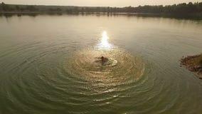 一个年轻人在湖扭转他的手在日落在slo mo 股票视频