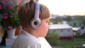 一个年轻人在窗口附近站立并且投入耳机听到音乐 与日落的被弄脏的背景,青少年 股票录像