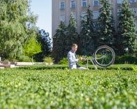 一个年轻人在管理的庭院里培养他的在机架的自行车 库存图片