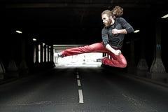 一个年轻人在街道做空手道跃迁 库存图片