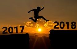 一个年轻人在2017年和2018年之间跳在太阳和通过在平衡五颜六色的天空的小山剪影空白 免版税图库摄影