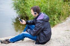 一个年轻人坐有电话的河岸并且听到与耳机的音乐 库存照片