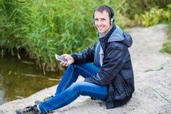 一个年轻人坐有电话的河岸并且听到与耳机的音乐 免版税库存图片