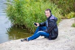 一个年轻人坐有电话的河岸并且听到与耳机的音乐 库存图片