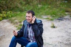 一个年轻人坐有电话的河岸并且听到与耳机的音乐 免版税库存照片