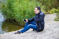 一个年轻人坐有电话的河岸并且听到与耳机的音乐 图库摄影