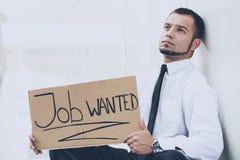 一个年轻人寻找一个工作 人看工作广告 希望的工作 免版税库存照片