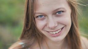 一个年轻人微笑的十六岁的女孩的画象有一朵雏菊花的在她的手上 有长的头发的棕色毛发的女孩 股票视频